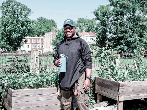 photo of Michael, armed with a reusable bottle full of refreshing Philly tap water, standing in his community garden, with Philly rowhomes in the background