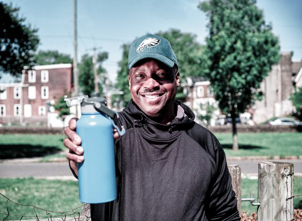 photo of Michael wearing an Eagles cap, standing in his neighborhood's community garden, holding out his reusable bottle of Philly tap water, with Philly rowhomes in the background